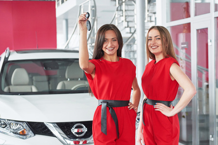 Young happy two woman near the car with keys in hand - concept of buying car.