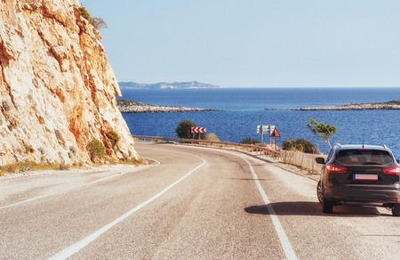 Fantastic paved road along the coast, and cars.