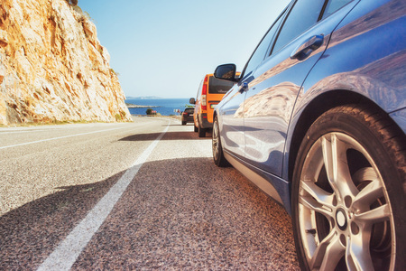 Fantastic paved road along the coast, and cars.