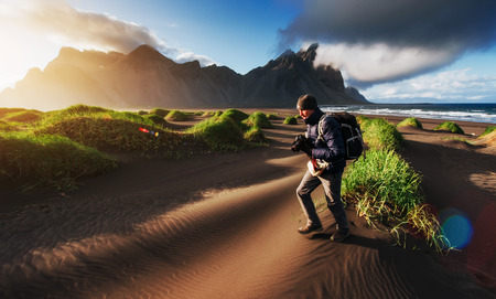 Fantastic west of the mountains and volcanic lava sand dunes to the beach Stokksness. Tourists traveling through the wilderness. Iceland Stock Photo