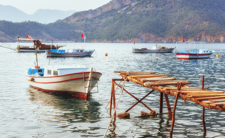 Boats near the broken pier, putting in a tranquil calm blue sea water.