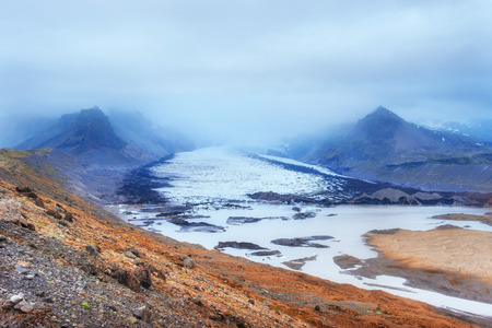 Gentle slopes of snow-capped mountains and glaciers. Wonderful Iceland in the spring