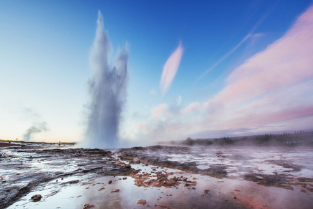Strokkur geyser éruption en Islande. Des couleurs fantastiques brillent à travers la vapeur. Beaux nuages ??roses dans un ciel bleu. Banque d'images - 85821745