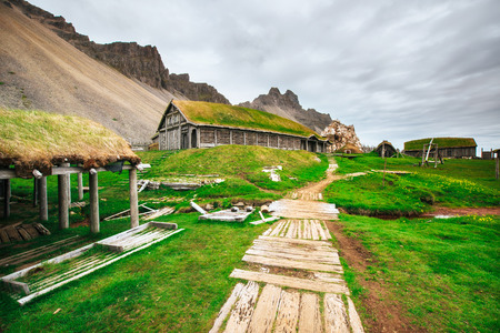 Traditional Viking village. Wooden houses near the mountain first settlements in Iceland Reklamní fotografie