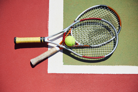 A tennis racket and new tennis ball on a freshly painted tennis court Banco de Imagens - 86264755