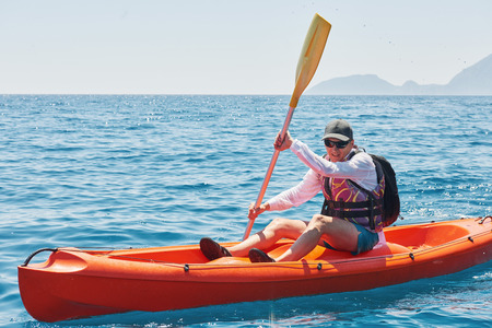 Boat kayaking near cliffs on a sunny day. Travel, sports concept. Lifestyle 版權商用圖片