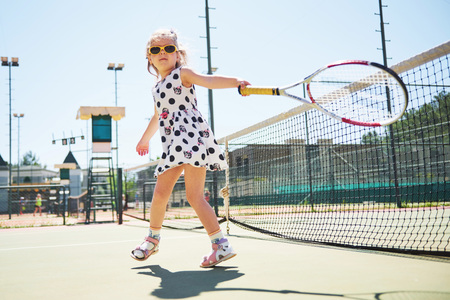 Cute girl playing tennis and posing for the camera