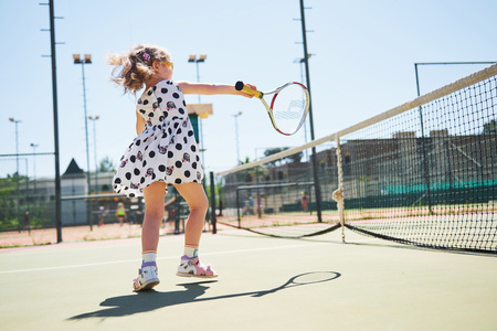 Cute girl playing tennis and posing for the camera Stock Photo - 86670498
