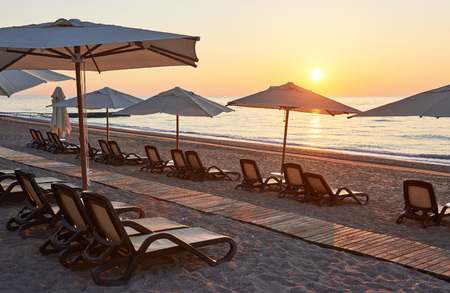 Scenic view of sandy beach on the beach with sun beds and umbrellas open against the sea and mountains. Hotel. Resort. Tekirova-Kemer