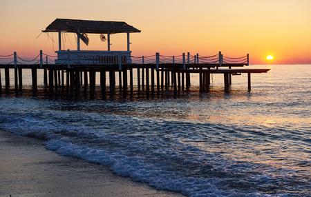 Pavillon auf dem hölzernen Pier in das Meer bei Sonnenuntergang Standard-Bild - 87233644