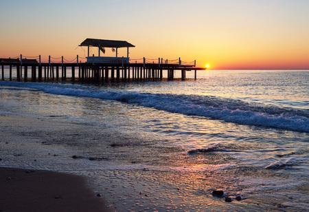 Pavillon auf dem hölzernen Pier ins Meer mit der Sonne bei Sonnenuntergang Standard-Bild - 87233646
