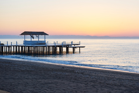 gazebo on the wooden pier into the sea with the sun at sunset
