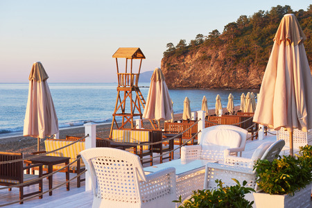 Scenic view of private sandy beach with sun beds and parasokamy the sea and mountains. Resort.