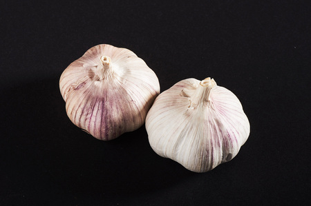 2 fresh garlic bulbs on a black background.
