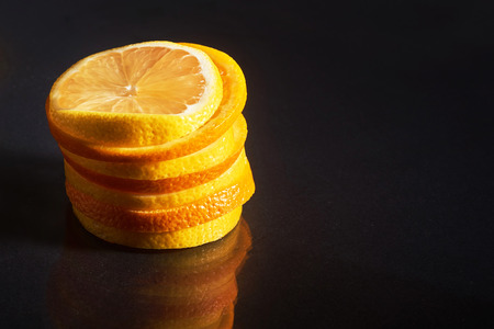 a stack of fresh orange and lemon isolated on a black background