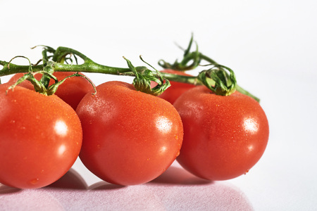 Branch of red organic tomatoes on a white background