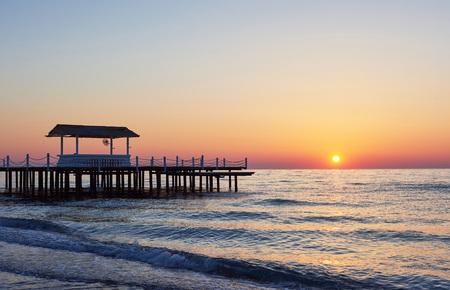 Wooden pier on a fancy orange sunset.