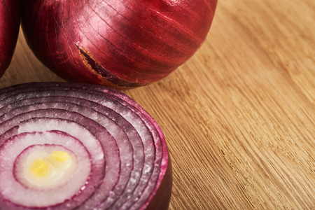 Half red onion on a wooden background