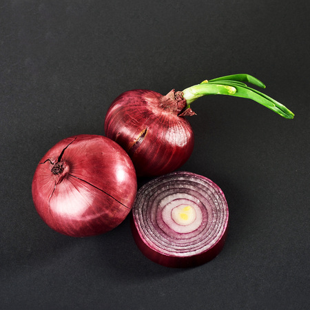 Red onions whole, isolated on a black background Imagens