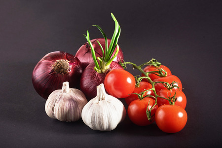 Tomatoes, onions and garlic are isolated on a black background. Stock fotó