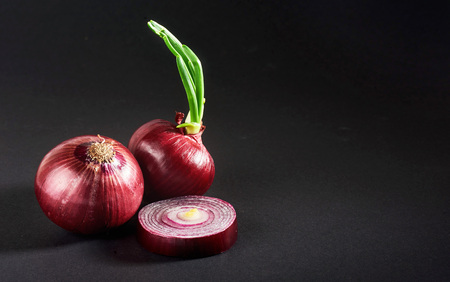 Red onions whole, isolated on a black background Stock Photo