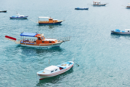 Boats float in the calm blue sea water in Turkey Imagens