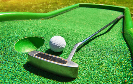 Golf ball and Golf Club on Artificial Grass Stock Photo