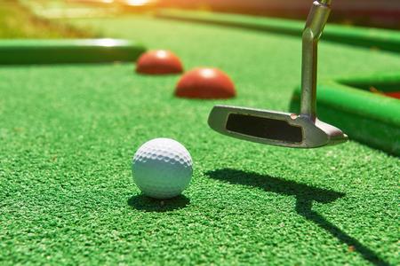 Golfbal en golfclub op kunstgras