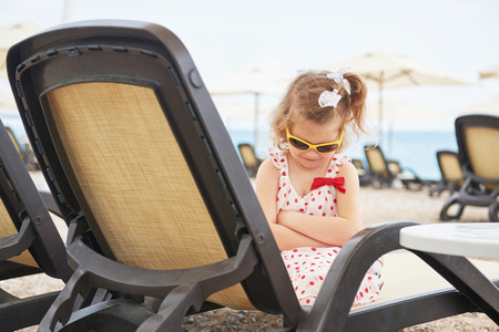 Little happy girl on the sunbeds by the sea, posing for the camera Stock Photo