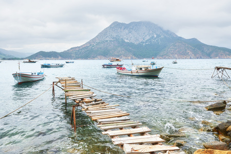 Boats near the broken pier, putting in a tranquil calm blue sea water Banco de Imagens