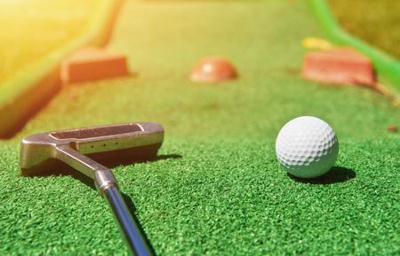 Mini-golf ball on artificial grass. Summertime.