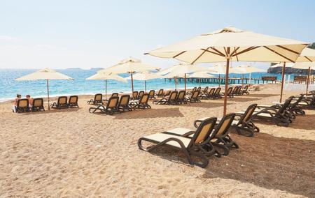 Scenic view of private sandy beach with sun beds from the sea and the mountains. Amara Dols Vita Luxury Hotel. Resort. Tekirova Kemer. Turkey. Stock Photo