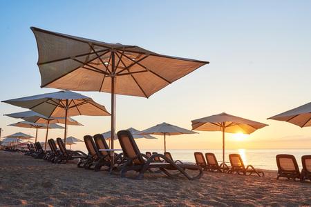 Scenic view of sandy beach with sun beds on the sea and mountains at sunset. Amara Dols Vita Luxury Hotel. Resort. Tekirova Kemer. Turkey Stock Photo