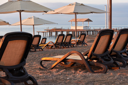 Scenic view of private sandy beach on the beach with sun beds against the sea and mountains. Amara Dolce Vita Luxury Hotel. Resort. Tekirova-Kemer