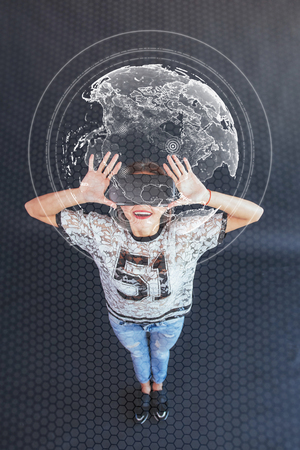 Young beautiful girl gets positive emotions using virtual reality goggles. The woman plays a game using augmented reality. Virtual world map.