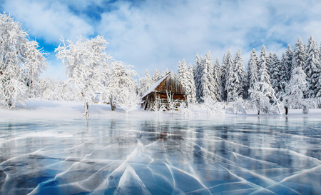 Blue ice and cracks on the surface of the ice. Frozen lake under a blue sky in the winter. Cabin in the mountains. Mysterious fog. Carpathians. Ukraine, Europe.