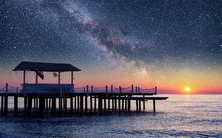 Fantastic starry sky Pier into the sea, used for natural background sea. Picturesque summer scene Banco de Imagens