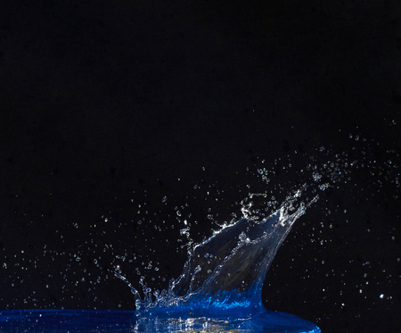 Splash of water crown on blue surface.