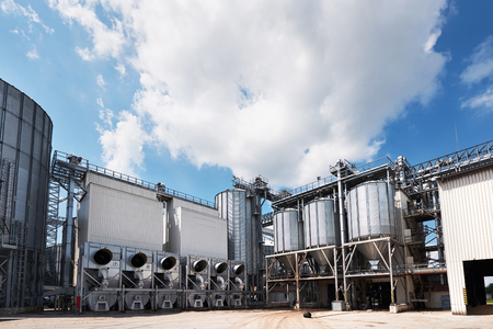 Agricultural Silos. Building Exterior. Storage and drying of grains, wheat, corn, soy, sunflower against the blue sky with white clouds Banco de Imagens