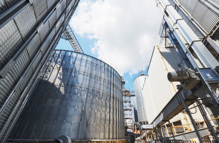 Agricultural Silos. Building Exterior. Storage and drying of grains, wheat, corn, soy, sunflower against the blue sky with white clouds Фото со стока