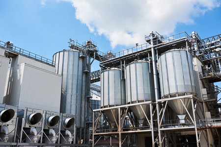 Agricultural Silos. Building Exterior. Storage and drying of grains, wheat, corn, soy, sunflower against the blue sky with white clouds Reklamní fotografie
