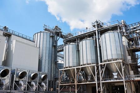 Silos agricoli. Esterno di un edificio Stoccaggio e asciugatura di cereali, grano, mais, soia, girasole contro il cielo blu con nuvole bianche Archivio Fotografico - 86477740