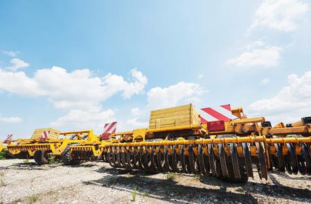 Sluit omhoog van zaaimachine in bijlage aan tractor op gebied. Landbouwmachines voor de lente werken die zaaien Stockfoto - 86477766