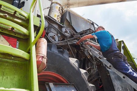 Combine machine service, mechanic repairing motor outdoors Banco de Imagens