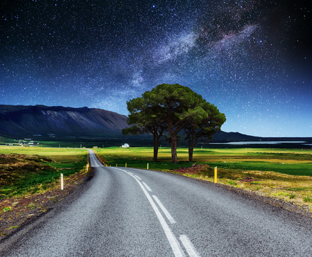 Asphalt road and lonely tree under a starry night sky and the Milky Way
