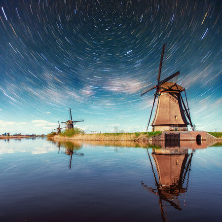 Colorful spring night with traditional Dutch windmills canal in Rotterdam. Wooden pier near the lake shore. Holland. Netherlands. Fantastic starry sky and the milky way. Stock Photo