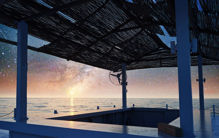 Scenic view of sandy beach on the beach with sun beds and umbrellas open against the sea and night sky. Fantastic starry sky and the milky way