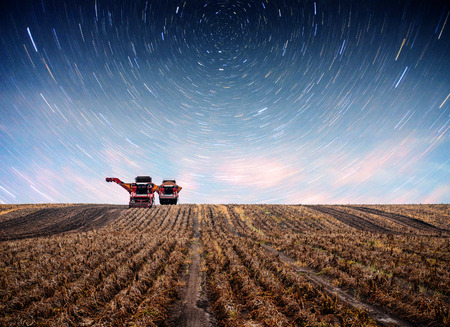 Tractor plowing farm field in preparation for spring planting. Fantastic starry sky and the milky way