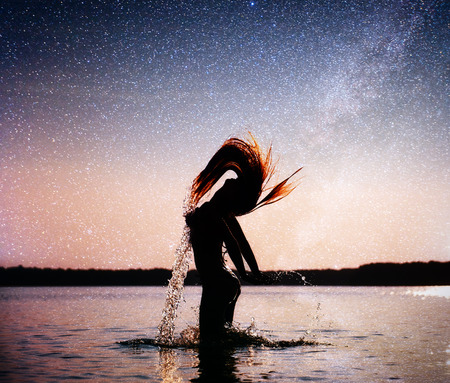 woman on water background at night sky. Fantastic starry sky and the milky way Stock Photo