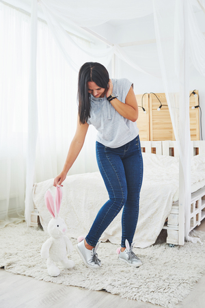 Happy easter. Beautiful sexy young woman wearing bunny ears on shoes and holding cute bunny toy Stock Photo